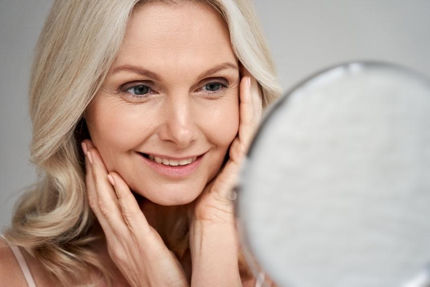 Frau betrachtet sich im Spiegel - Biodroga Golden Caviar 24-h-Pflege